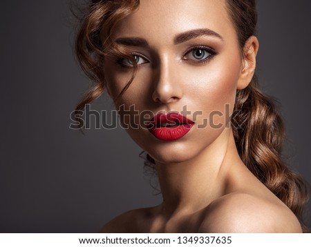 Beautiful face of young woman with red lipstick. Portrait of a stunning sexy girl looks at camera. Attractive model with stylish makeup.  Closeup portrait of a caucasian female.  #1349337635