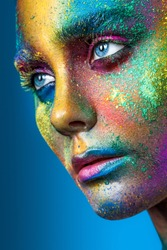 Beautiful face with colored powder on a blue background