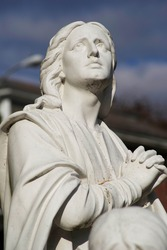 Beautiful facial expression on Mary Magdalen, her hands clasped in prayer in this old cemetery statue.