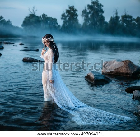 Beautiful fairy in a beautiful dress, standing in water looking at sinking plume among large stones in water.A wreath made of shells, handmade.Foggy forest.Mystical photo shoot.Fashionable toning.