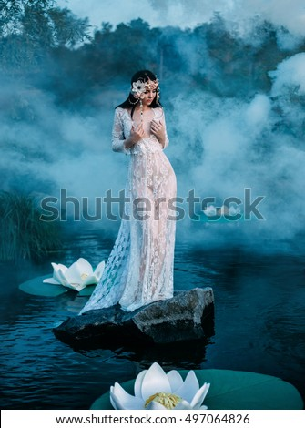 Beautiful fairy in a beautiful white garment, sits on a rock in water. A wreath made of shells, handmade. Among picturesque forests, mysterious  lakes. Mystical photo shoot. Fashionable toning.