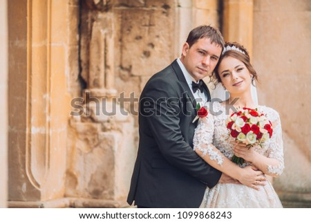 Beautiful fairytale newlywed couple hugging near old medieval castle. Wedding day for adorable newlyweds couple. Man and woomen hug and kiss aech other near old ancient door. Foto stock ©