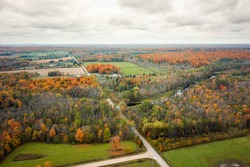 Beautiful fall aerial photograph of farm land, river and woods in Wisconsin during peak autumn colors with green tree leaves turning orange, yellow, and red and fluffy white clouds in the sky above.