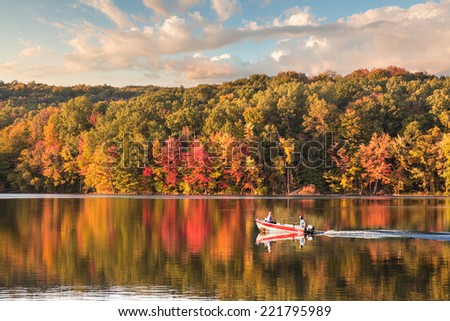 beautiful fall reflections in a lake with a fishing boat during sunset