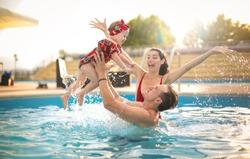 Beautiful family having fun in a swimming pool