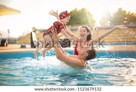 Beautiful family having fun in a swimming pool #1123679132