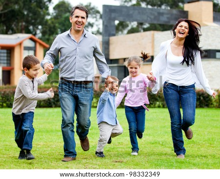 Beautiful family having fun running outdoors and smiling