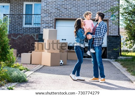 beautiful family in front of new house with many boxes standing on pathway to garage