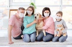 Beautiful family in medical masks against coronavirus at home