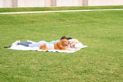 Beautiful family is having rest with dog outdoors. Housband and wife are lying with dog labrador on green grass in park.
