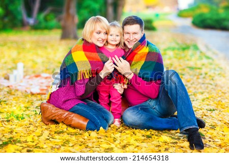 Beautiful family keep warm under a blanket in the autumn park. Fun and games in nature.