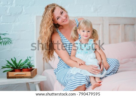 beautiful family mom and daughter are sitting on the bed and smiling