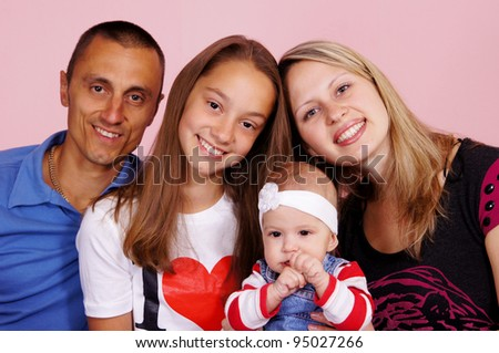 beautiful family of four people sitting on a pink background