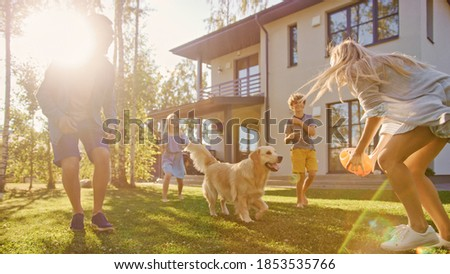 Beautiful Family of Four Play Catch Toy Ball with Happy Golden Retriever Dog on the Backyard Lawn. Idyllic Family Has Fun with Loyal Pedigree Dog Outdoors in Summer House Backyard.