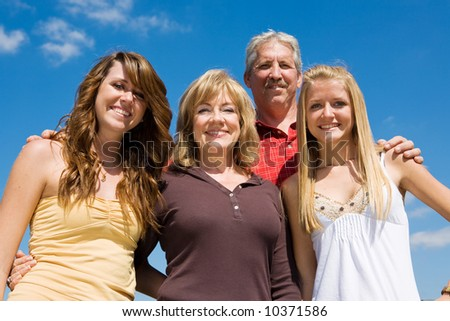 Beautiful family of grandparents and granddaughters against a blue sky.