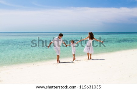 Beautiful family of three dancing on a tropical beach