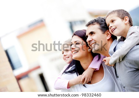 Beautiful family outside their house looking away