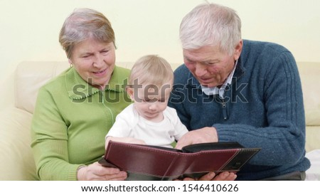 Beautiful family portrait, grandparents showing to baby photo album, share generations memories, child sitting in grandmother lap on couch, heme feeling