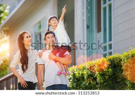Beautiful family portrait smiling outside their new house with sunset