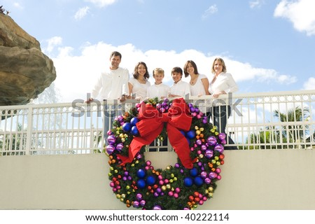 Beautiful Family posing by Christmas wreath with bow