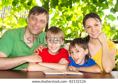 beautiful family reading a book at nature