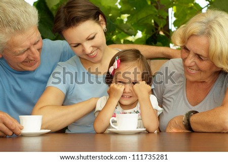 Beautiful family sitting on the veranda of his cottage