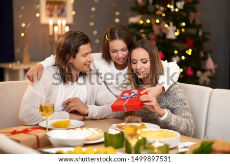 Beautiful family with presents sharing presents during Christmas dinner