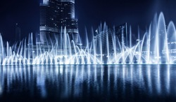 Beautiful famous fountain in Dubai at night, romantic music, water dance, blue lights, luxury resort, evening cityscape
