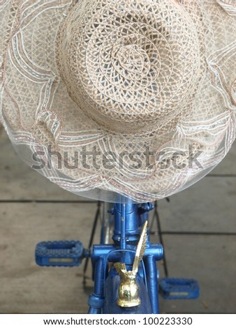 beautiful fancy hat hang on a bike for protect the heat of sunny day
