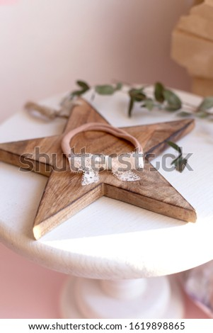 Beautiful fashion accessory for baby girls. Handmade accessories lace and stars on elastic band on white and brown background. Concept of children's clothing