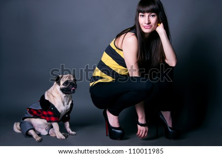 Beautiful fashion girl in black leggings, stripped t-shirt and high heels with her favorite pug dog pet in funny costume against grey background