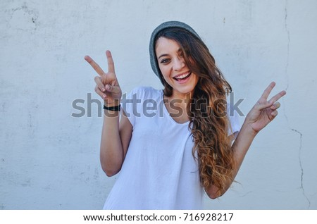 Shutterstock Beautiful fashion girl model, wearing casual basic look, with white t-shirt and grey cap, happiness