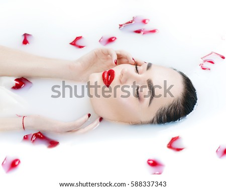 Beautiful Fashion model girl in milk bath, touching face skin, spa and skin care concept. Beauty young Woman with red rose flower relaxing in milk bath. Healthy Face and hands, rejuvenation. - Shutterstock ID 588337343