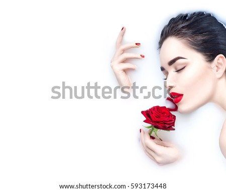 Beautiful Fashion model girl taking milk bath, spa and skin care concept. Beauty young Woman with bright makeup and red rose flower relaxing in milk bath. Healthy Face and hands, red nails and lips - Shutterstock ID 593173448