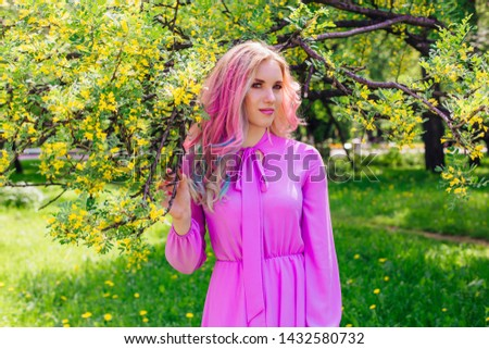 Beautiful fashion model girl with colorful dyed hair and perfect makeup and hairstyle standig next to blooming barberry bush with yellow flowers #1432580732