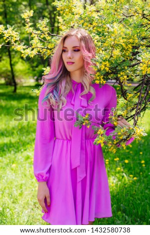 Beautiful fashion model girl with colorful dyed hair and perfect makeup and hairstyle standig next to blooming barberry bush with yellow flowers #1432580738