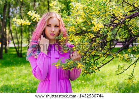 Beautiful fashion model girl with colorful dyed hair and perfect makeup and hairstyle standig next to blooming barberry bush with yellow flowers #1432580744