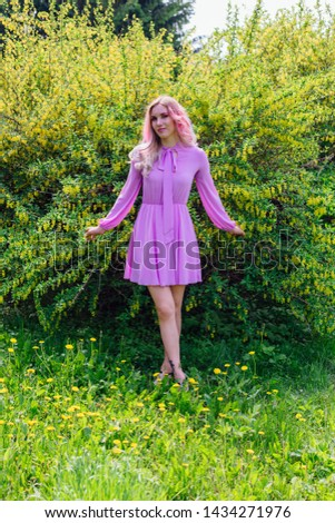 Beautiful fashion model girl with colorful dyed hair and perfect makeup and hairstyle standig next to blooming barberry bush with yellow flowers #1434271976