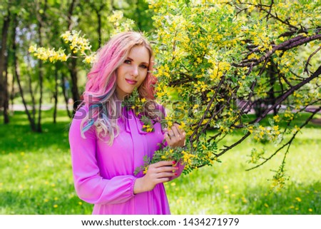Beautiful fashion model girl with colorful dyed hair and perfect makeup and hairstyle standig next to blooming barberry bush with yellow flowers #1434271979
