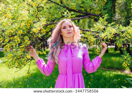 Beautiful fashion model girl with colorful dyed hair and perfect makeup and hairstyle standig next to blooming barberry bush with yellow flowers #1447758506