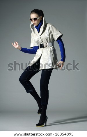 Beautiful fashion model in autumn clothes posing over white background - stock photo