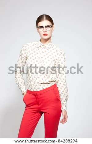 Beautiful fashion model in tunic, red pants and glasses on white background