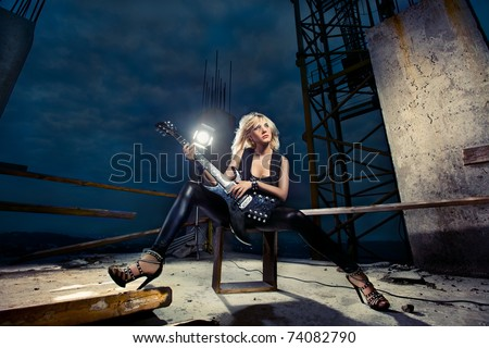 beautiful fashion model playing guitar on a roof top