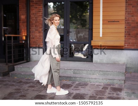 Beautiful Fashion Model smiling on City Street. Stylish Woman Wearing Fashionable Spring or Autumn Clothes (beige trench coat, oversize khaki cargo pants, accessorie) Outdoors. Trend outfit #1505792135
