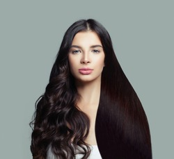 Beautiful fashion model woman with long straight hair and perfect curly hairstyle on blue background