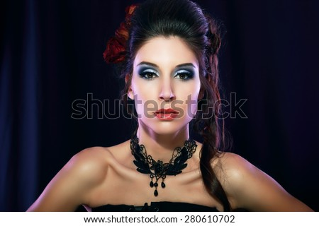 beautiful fashion vampire victorian style woman posing over dark background