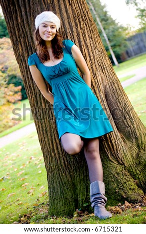 beautiful fashion woman in a park leaning against a tree