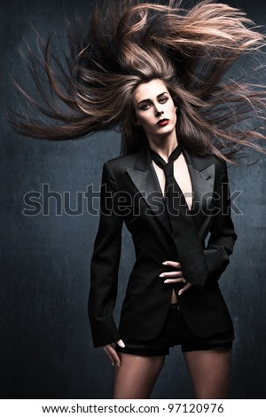 beautiful fashion woman model in tuxedo jacket, tie with long flying hair