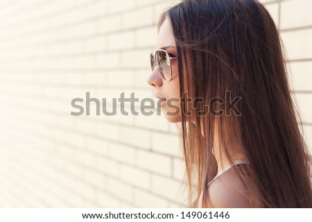 Beautiful fashionable attractive girl in glasses close up in profile