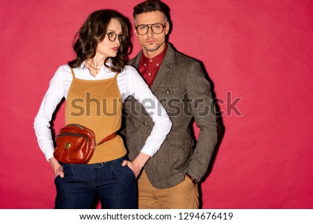 beautiful fashionable couple in formal wear and glasses posing on red background #1294676419